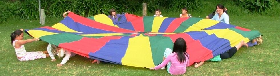 Um grupo de crianças, sentadas em roda, brincam com um pano colorido