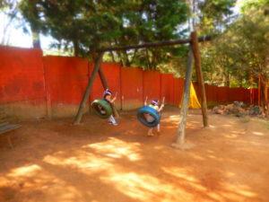 Crianças brincam no amplo espaço verde do Viverzinho, unidade da Educação Infantil.