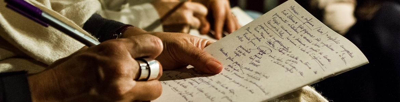 A foto mostra uma mão segurando uma caneta e escrevendo em um papel