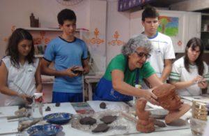 Uma mulher de cabelos brancos e quatro alunos alunos estão trabalhando com argila