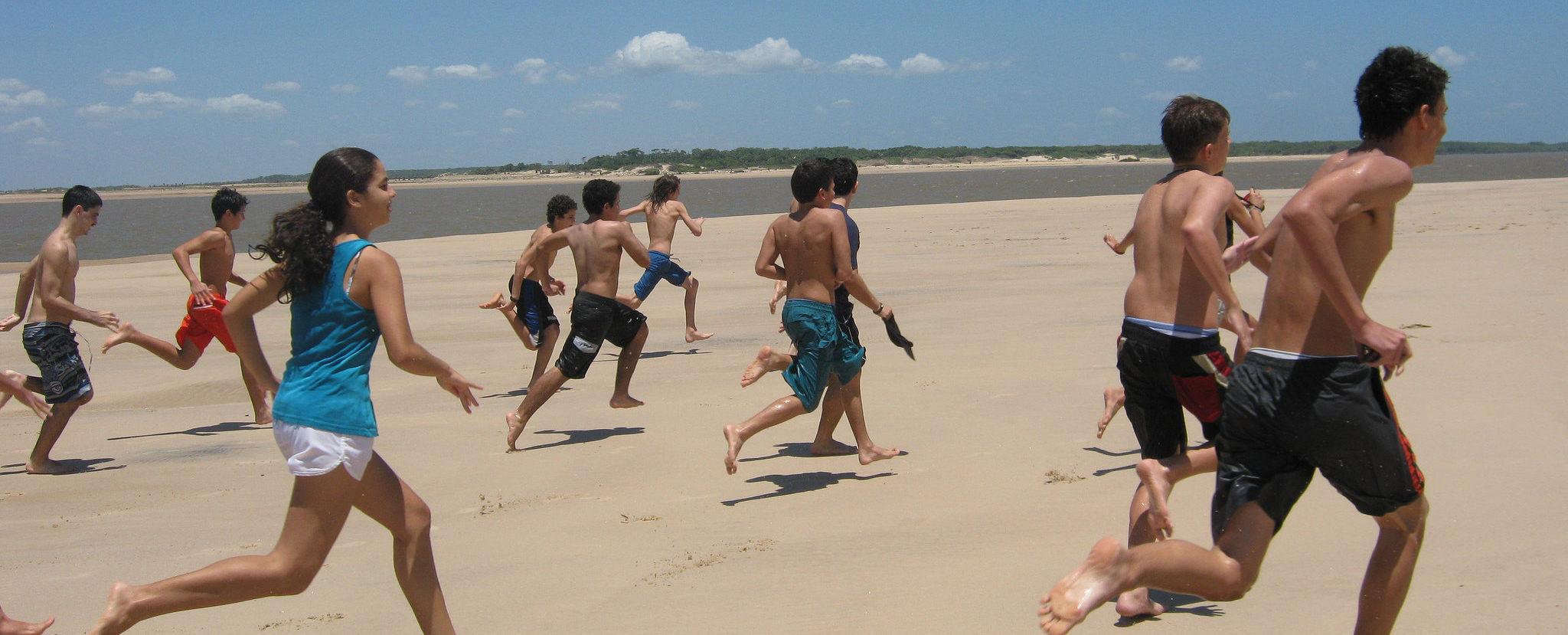 Imagem de várias crianças da Escola Vila correndo da orla da praia