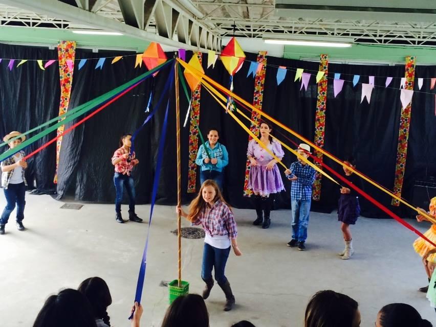 Crianças vestidas em trajes juninos: camisas xadrez, saias rendadas e tranças. Elas dançam no centro de uma roda e o local está decorado com fitas coloridas e bandeirinhas de festa junina.