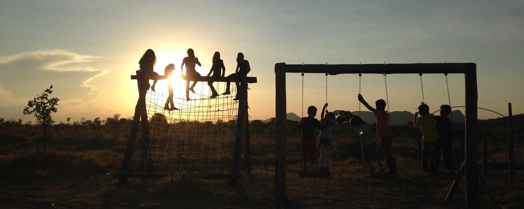 A fotografia mostra crianças brincando em um balanço e em um trepa-trepa. Elas estão contra a luz durante o pôr-do-Sol