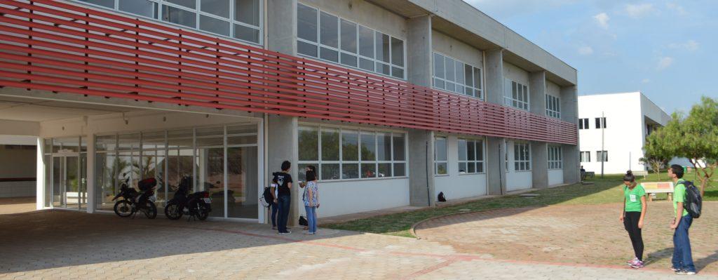 A foto mostra a fachada do IFPR: um prédio de dois andares com janelas brancas com detalhes vermelhos de metal entre elas