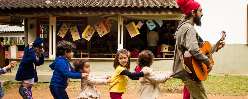 Crianças brincam de trenzinho, conduzidas por um adulto. Eles estão em um espaço aberto, de chão batido.