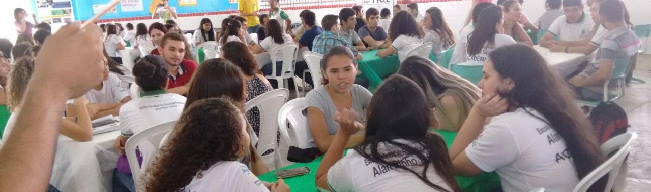 Em um salão grande, estudantes estão sentados em volta de mesas de plástico.