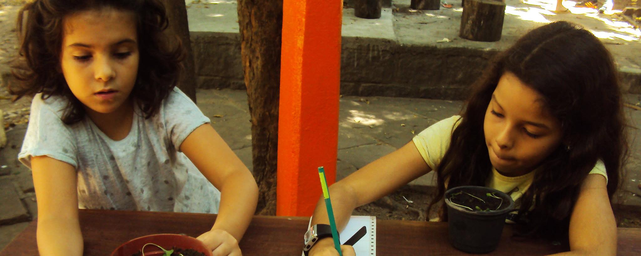 Duas crianças estão sentadas em uma mesa e desenham em folhas de papel.