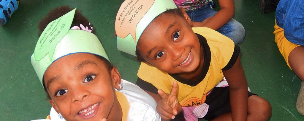 Na foto estão duas crianças sorrindo. A câmera está posicionada no alto. As crianças usam uma faixa de papel em volta da cabeça.