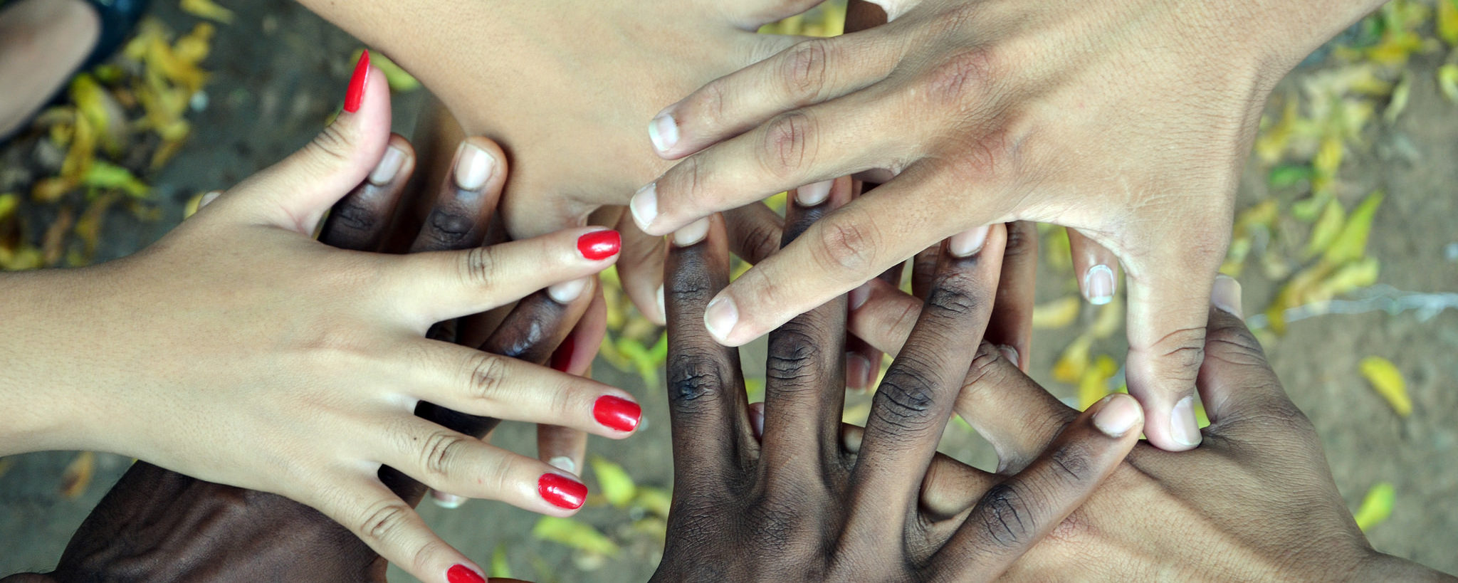 Na foto há cinco mãos negras e brancas entrelaçadas e sobrepostas.