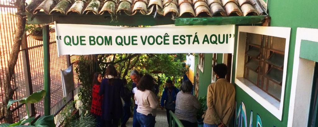 Na foto, pessoas estão caminhando e entrando na escola. Na entrada da escola, há um grande cartaz com os dizeres: