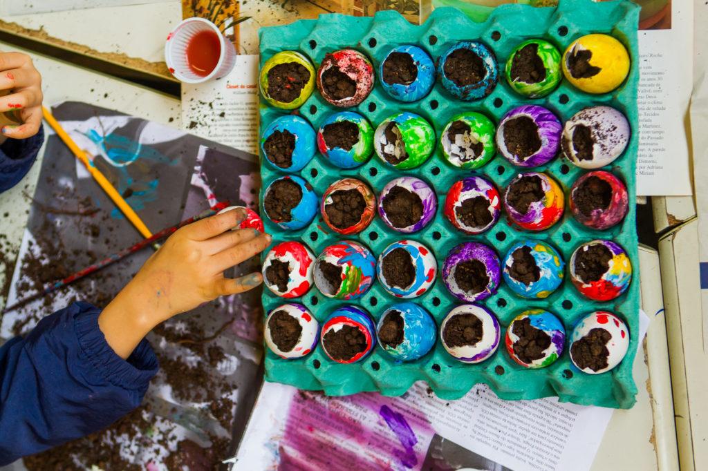 Na imagem, uma criança reutiliza cascas de ovos coloridas como vaso para plantinhas.