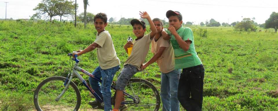 Quatro garotos posam para a foto. Dois estão em uma mesma bicicleta e os outros dois estão atrás. A paisagem é de um campo verde bem vasto.
