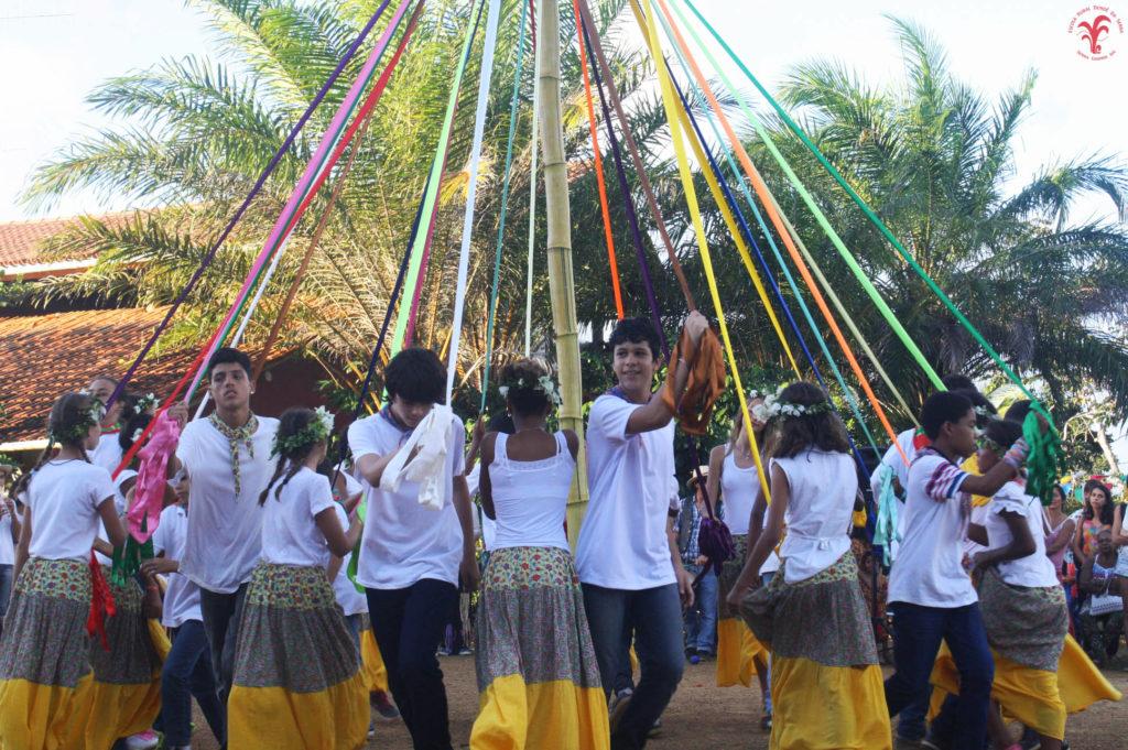 A foto mostra um grupo de estudantes dançando ao redor de um tronco onde estão amarradas fitas coloridas