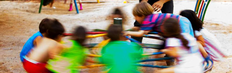 Imagem de um gira-gira bem colorido com crianças brincando nele. A imagem está borrada, dando ideia de movimento.