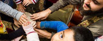 a imagem mostra um grupo de crianças e um adulto. Eles estão em roda e com um dos braços esticados para frente, tocando um objeto comum.