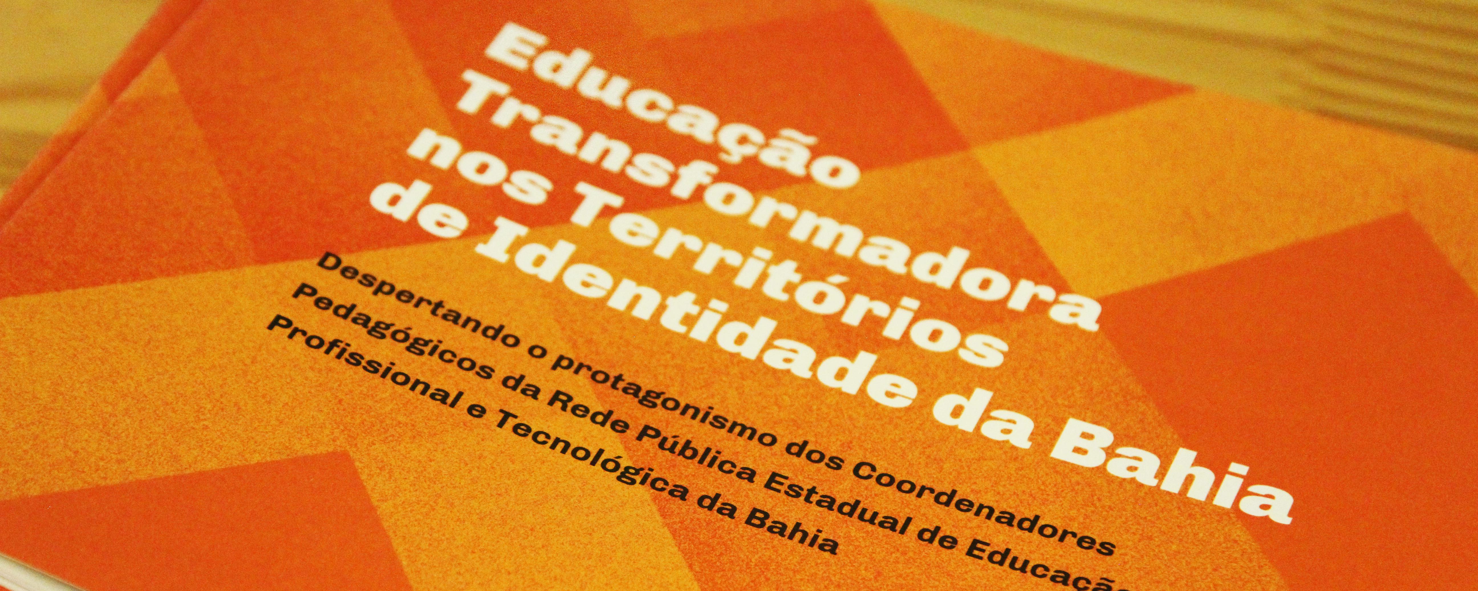 """Foto da capa da publicação """"Educação transformadora nos territórios de identidade da Bahia"""". A capa é laranja, com texto em branco e preto."""