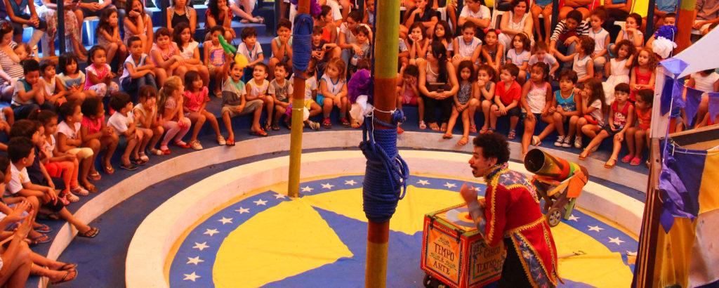 A foto mostra um grupo de crianças. Elas estão sentadas em uma arquibancada em um circo. No centro, há um homem.