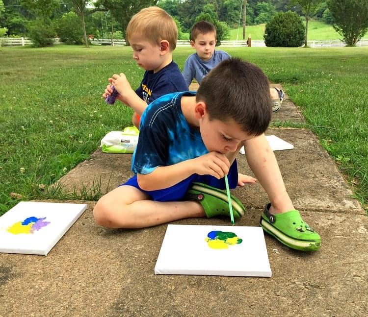 Três crianças estão sentadas no chão uma atrás da outra. Elas estão pintando. Com um canudinho na boca, elas miram para o papel sujo de tinta e assopram.
