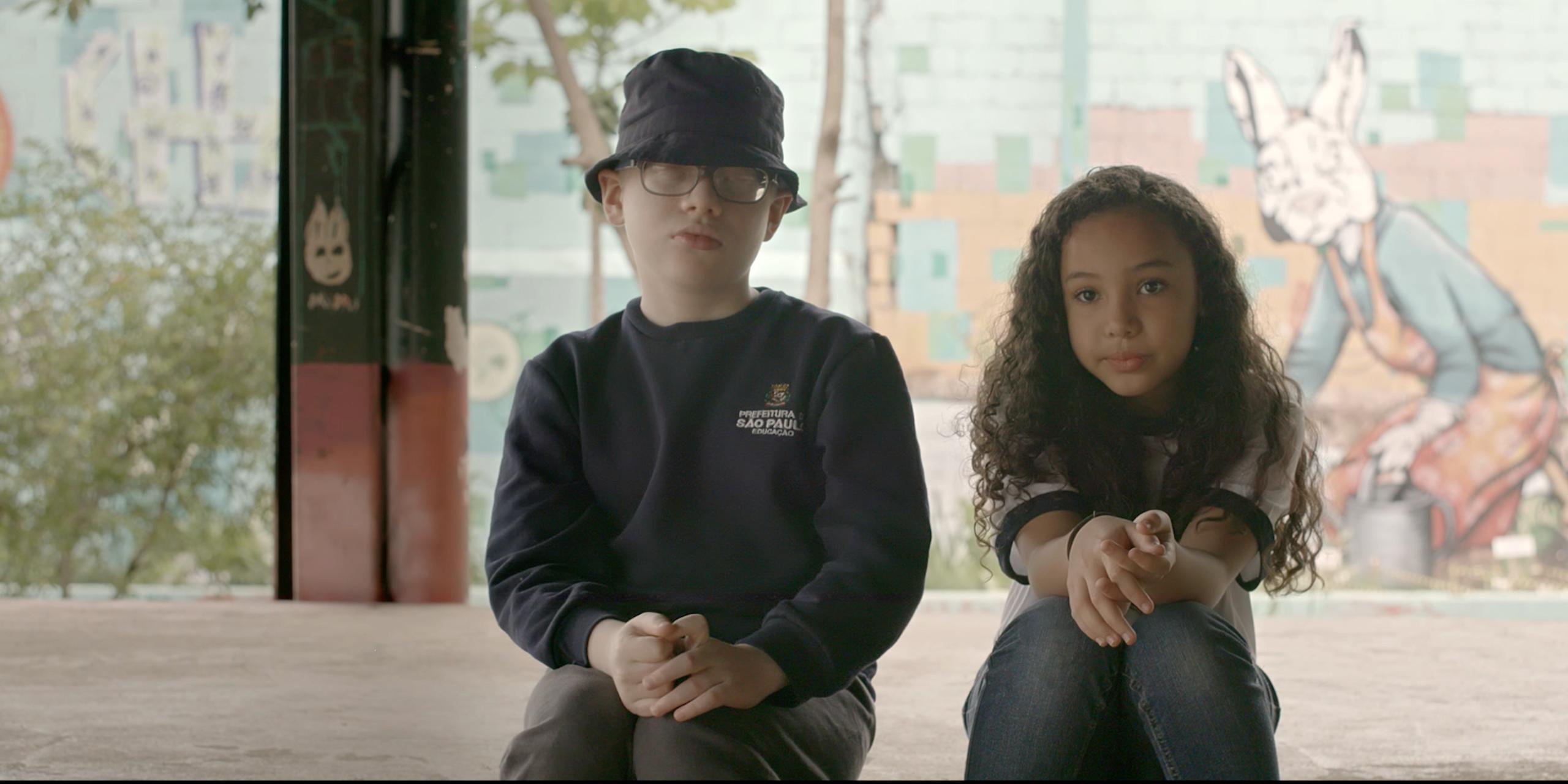 Duas crianças estão sentadas uma ao lado da outra, olhando para a câmera.
