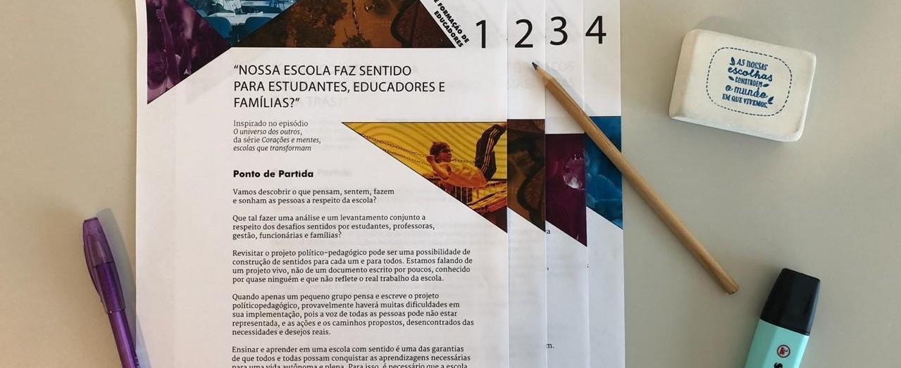 Foto mostra os quatro planos de formação de educadores impressos, dispostos em uma mesa.