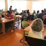 Em um auditório, várias pessoas conversam, em pequenos grupos.