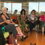 Em um auditório, um grupo de pessoas está sentado em roda, conversando.