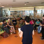 Em um auditório, um grupo de pessoas conversa.