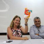"""Uma mulher e um homem sorriem para a foto. A mulher segura um exemplo do livro """"O ser e o agir transformador"""""""