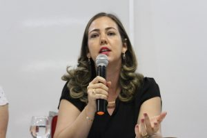 Uma mulher de cabelos castanhos fala ao microfone.