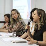 Uma mulher fala ao microfone. Ao seu lado, três mulheres a observam.
