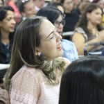 Uma mulher de cabelos curtos, que está na plateia, sorri.