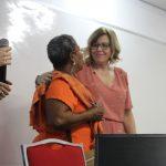 Duas mulheres se olham e se abraçam.