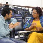 Um homem e uma mulher conversam. Eles se olham, atentos.