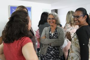 Um grupo de mulheres conversa e sorri.