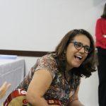 Uma mulher sorri, com um violão no colo.