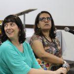 Duas mulheres, uma ao lado da outra. Uma delas olha para o lado e a outra segura um violão.