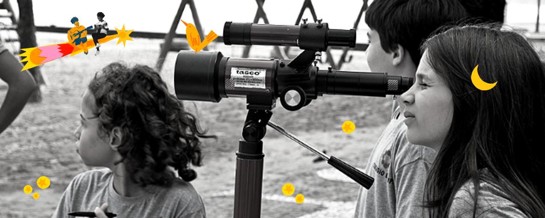 na imagem em preto e branco, três crianças olham por um telescópio. Por toda a foto, em colorido, há ilustrações de pássaros, luas, estrelas e crianças viajando em uma estrela cadente.
