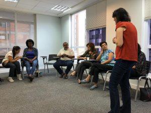 Grupo de pessoas sentadas em semicírculo. Uma mulher está de pé, guiando a conversa.