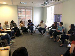 Um grupo de pessoas está sentado em círculo conversando.