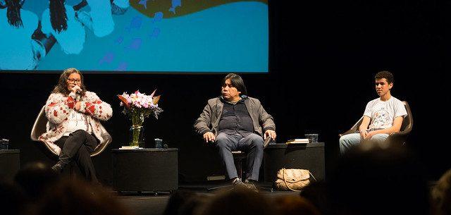 Três pessoas, uma mulher, um homem e um adolescente, estão sentados. Eles estão em um palco, acompanhado de flores. À esquerda, a mulher fala ao microfone.