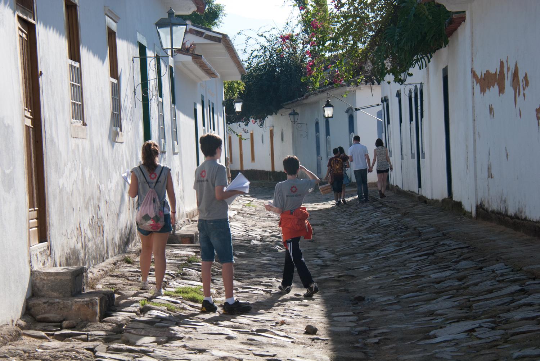 Eles estão em uma parte  histórica da cidade, caminhando entre casas.