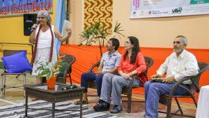 Na fotografia há quatro adultos. Três deles estão sentados enquanto uma mulher, de pé, fala o microfone.