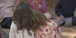a imagem mostra duas crianças de costas sentadas lado a lado. Uma delas apoia a cabeça no ombro da outra.