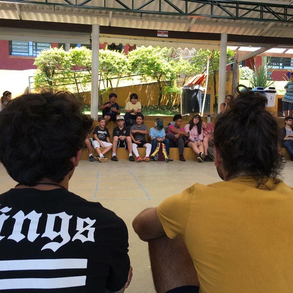 Em um pátio, um grupo de estudantes está sentado em círculo, conversando