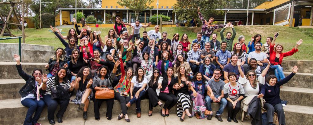 Um grupo com cerca de 30 pessoas, sentada em uma arquibancada, sorri para a foto. Algumas delas abrem os braços.