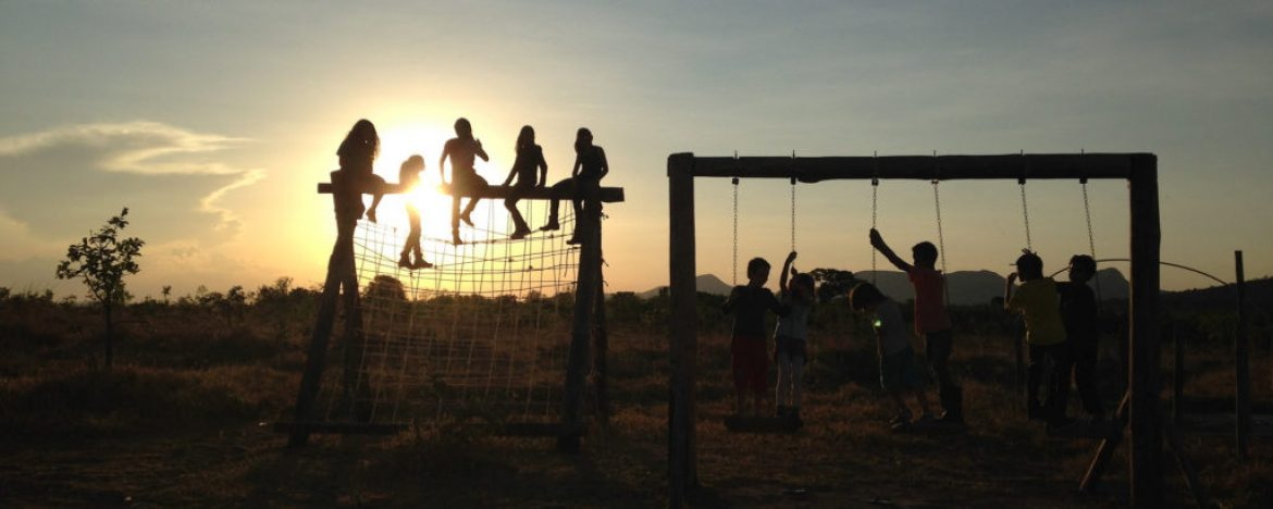 Children playing on the swing. Landscape in the back of the sunset.